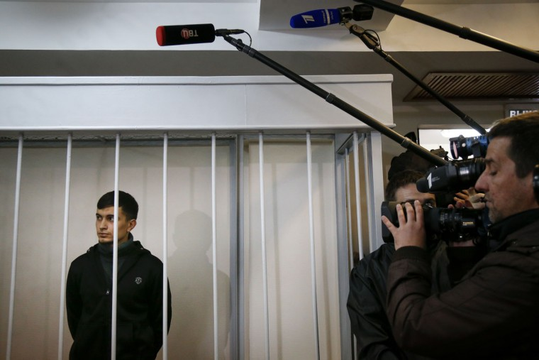 Aslan Baisultanov, a man suspected of plotting a terrorist attack in Moscow, stands in a defendants' cage in a court room in Moscow, Russia, Tuesday, Oct. 13, 2015. Security officials said the suspects arrested Sunday were trained by the Islamic State group and had planned a terror attack on the Moscow public transport system. (AP Photo/Alexander Zemlianichenko)