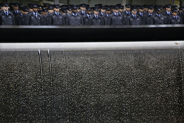 Probationary New York firefighters stand at attention at the Sept. 11 Memorial during a wreath laying ceremony, Wednesday, Oct. 28, 2015 in New York. The FDNYís 300 probationary firefighters participated in the ceremony to honor the fathers of two classmates who were killed in the attacks of Sept. 11, 2001. (AP Photo/Mark Lennihan)