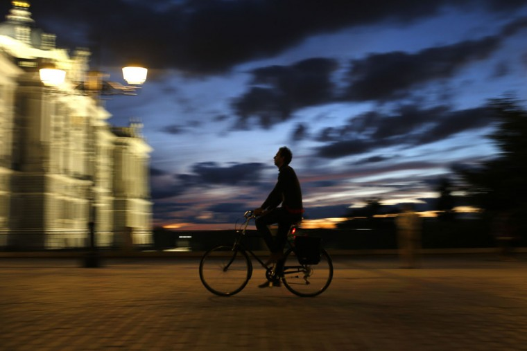 A man rides a bicycle as the sun sets at the Oriente square in Madrid, Spain, Tuesday, Oct. 6, 2015. The square is a novel area of the Spanish capital flanked by the Royal Palace and the Opera house. (AP Photo/Francisco Seco)