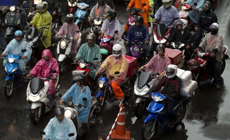 Motorcyclists wait at a major intersection through heavy rain in central Bangkok, Thailand, Friday, Oct. 2, 2015. Thailand's rainy season typically runs from July to October. (AP Photo/Mark Baker)