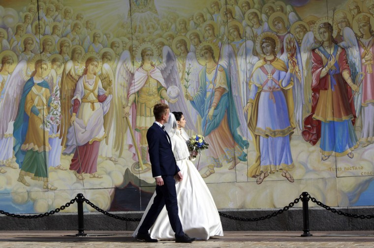 A newly wedded couple pass the wall of St. Michael's Cathedral in Ukraine's capital, Kiev, Saturday, Oct. 10, 2015. (AP Photo/Sergei Chuzavkov)