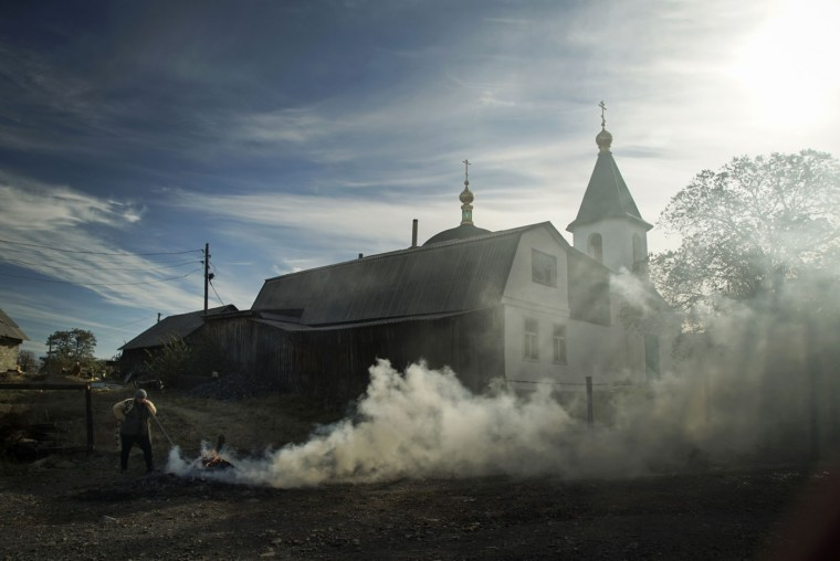 A local woman burns dry grass by the Orthodox Church near the crash site of the Malaysia Airlines Flight 17 in the village of Hrabove, eastern Ukraine, Tuesday, Oct. 13, 2015. The Dutch Safety Board is publishing its final report Tuesday into what caused Malaysia Airlines Flight 17 to break up high over Eastern Ukraine last year, killing all 298 people on board. (AP Photo/Mstyslav Chernov)