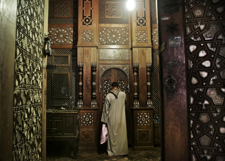 CORRECTS NAME OF THE SHRINE FROM AHMED AL- RIFA'I TO AHMED EZZ ELDIN AL-RIFA'I: A man prays in front of the shrine of Ahmed Ezz Eldin al-Rifa'i, one of the grandchildren of late Iraqi Muslim Sufi Saint Ahmed al-Rifa'i, inside the Al-Rifa'i Mosque in Cairo, Egypt, Wednesday, Oct. 7, 2015. The mosque was named after Al-Rifa'i who was the founder of the Sufi Rifai order. (AP Photo/Nariman El-Mofty)