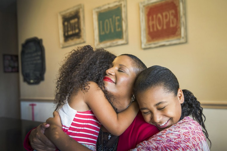 Breast cancer survivor Noelle LeVeaux, center, snuggles at home with her daughters Jordan, left, and Sydney, in Plano, Texas. LeVeaux's breast cancer diagnosis had a ripple effect on daughters Jordan, 7, and Sydney, 11. During cancer treatment, Sydney tucked her in at bedtime and left water on her nightstand. Jordan asked if cancer was contagious. (Smiley N. Pool/The Dallas Morning News via AP)