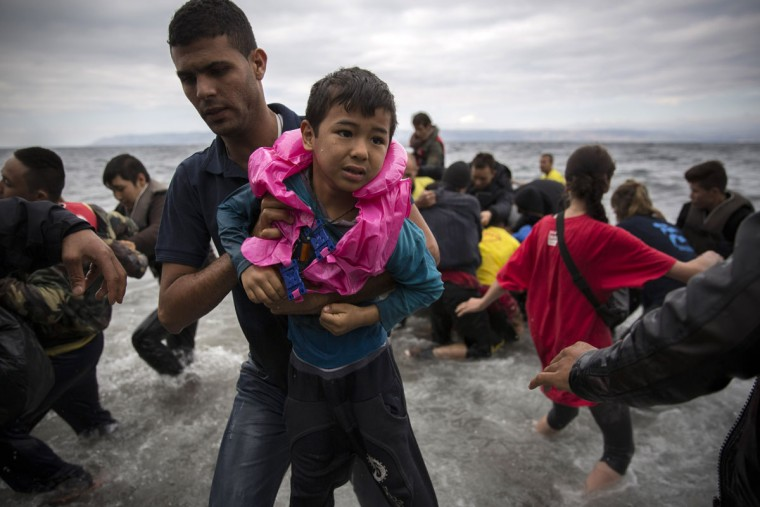 A volunteer holds an Afghan child after arriving with a group of migrants on a dinghy from the Turkish coast to the northeastern Greek island of Lesbos, on Wednesday, Sept. 30, 2015. Authorities in Greece say 2 people have died and 47 people have been rescued from a dinghy near the island on Wednesday. Lesbos is the busiest entry point for migrants reaching the European Union, with some 2,000 arrivals per day from nearby Turkey. (AP Photo/Santi Palacios)