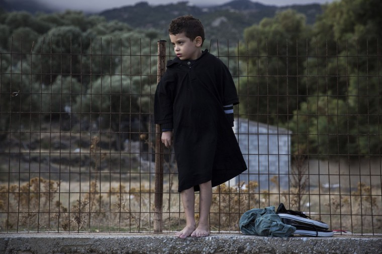 A barefoot boy stands on a cement wall after his family's arrival on a dinghy from the Turkish coasts to the northeastern Greek island of Lesbos, on Wednesday, Sept. 30, 2015.The International Organization for Migration says a record number of people have crossed the Mediterranean into Europe this year, now topping a half a million, with some 388,000 entering via Greece.(AP Photo/Santi Palacios)