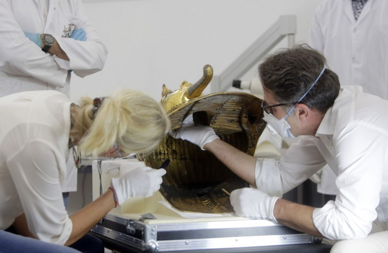 German restorers Christian Eckmann and Katja Broschat begin work on the restoration of the famed golden mask of King Tutankhamun at the Egyptian Museum, in Cairo, Egypt, Tuesday, Oct. 20, 2015. (AP Photo/Amr Nabil)