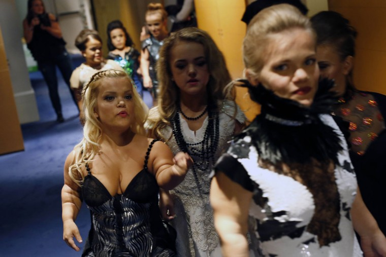 Models get ready before hitting the catwalk at the French Ministry of Culture during the dwarf fashion show in Paris, France, Friday Oct. 2, 2015. The show is an event organizers say is aimed at highlighting the elitism and prejudice that the model industry encourages in its depiction of bodies. It is presented during the Paris Fashion Week but is not part of it. (AP Photo/Jerome Delay)