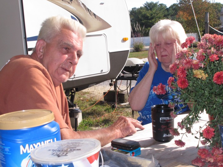 In this Oct. 21, 2015, photo, Bob Collis, left, and his wife, Katherine, right, sit in front of their trailer in Berkeley Township, N.J. They have been unable to return to their home in Toms River, N.J., since Superstorm Sandy damaged it three years ago. (AP Photo/Wayne Parry)