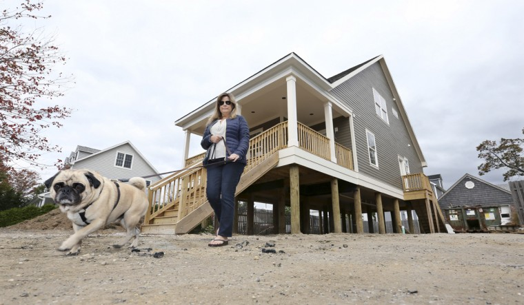 In this Saturday, Oct. 24, 2015, photo, Michelle Petrow walks with her dog, Rudy, outside her home three years after her former home on the site was destroyed by Superstorm Sandy, in Manasquan, N.J. The single mother of three, who needs a kidney transplant, is still rebuilding after years of fighting with insurers, contractors and state aid programs. But she's not even sure she'll be able to move in to the new home rising 15 feet higher than her old one: her bank is foreclosing on it because she stopped making payments for a year and a half while she simultaneously rented an apartment. (AP Photo/Mel Evans)