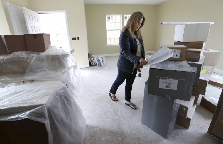 In this Saturday, Oct. 24, 2015, photo, Michelle Petrow looks through building materials in her home, three years after her former home on the site was destroyed by Superstorm Sandy, in Manasquan, N.J. The single mother of three, who needs a kidney transplant, is still rebuilding after years of fighting with insurers, contractors and state aid programs. But she's not even sure she'll be able to move in to the new home rising 15 feet higher than her old one: her bank is foreclosing on it because she stopped making payments for a year and a half while she simultaneously rented an apartment. (AP Photo/Mel Evans)