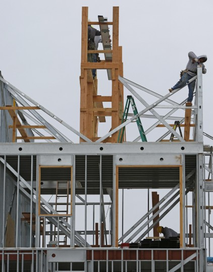 "Construction workers build the framework for a house near the beach in Belle Harbor before the third anniversary of Superstorm Sandy, Tuesday, Oct. 27, 2015, in New York. Homes closest to the Atlantic Ecean were heavily damaged by storm surge and floodwaters from the ""hundred-year storm."" (AP Photo/Kathy Willens)"