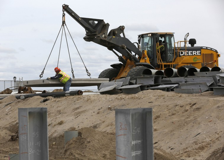A worker stabilizes a pre-cast concrete slab while a co-worker uses a crane to position it on a berm as construction continues on replacement portions of the Rockaway Beach boardwalk Tuesday, Oct. 27, 2015, in New York, before the third anniversary of Superstorm Sandy. Since the storm, more than $140 million has been invested to repair and restore damaged areas of Rockaway Beach, including the boardwalk, beach buildings, and to construct new facilities for the public. (AP Photo/Kathy Willens)
