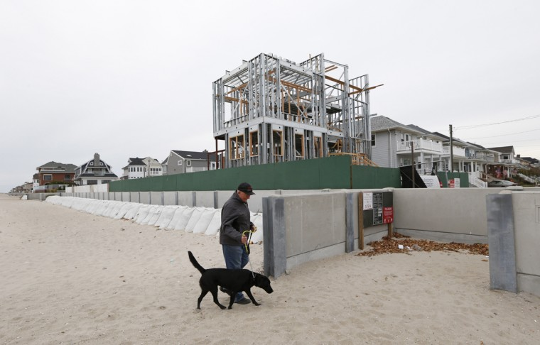 Newly constructed homes replacing those destroyed in Superstorm Sandy tower on the horizon as Belle Harbor resident Larry Racioppo walks his dog Juno near Beach 131st Street before the storm's third anniversary, Tuesday, Oct. 27, 2015, in New York. A 5-foot-high concrete retaining wall buttressed by sandbags has been added as further protection against the encroaching ocean for the homes on the opposite side of the wall. (AP Photo/Kathy Willens)
