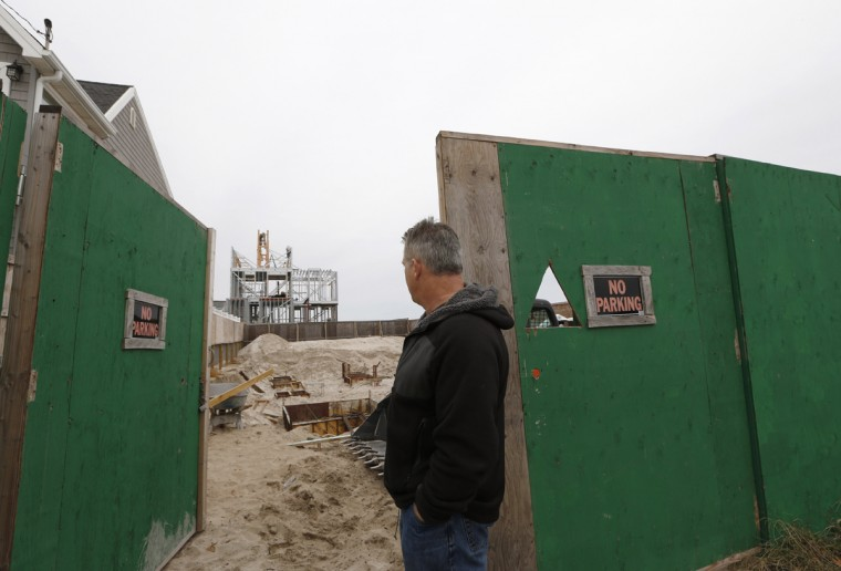 Retired firefighter Robert Ostrander looks at construction on his new home at Beach 132nd Street in Belle Harbor, a replacement for his former house which was destroyed by a storm surge from Superstorm Sandy, Tuesday, Oct. 27, 2015, in New York, before the third anniversary of the storm. (AP Photo/Kathy Willens)