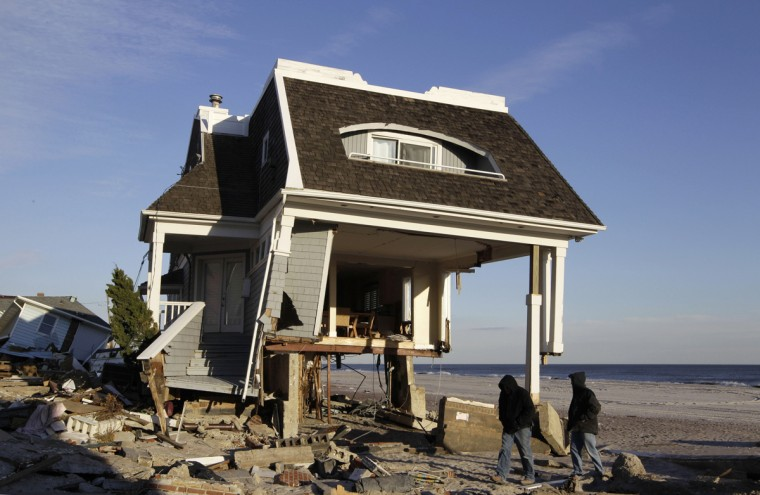 In this Dec. 5, 2012, file photo, men walk past the Superstorm Sandy destroyed Belle Harbor home in New York belonging to now-retired firefighter Robert Ostrander. On the three-year anniversary of the storm, Ostrander is still rebuilding his beachfront home. Construction above the foundation is just beginning. (AP Photo/Kathy Willens, File)