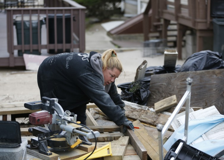 "Habitat for Humanity employee Anna Acosta works on reconstructing the deck of a Breezy Point bungalow before the third anniversary of Superstorm Sandy, Tuesday, Oct. 27, 2015, in New York. Acosta and her husband, Reynaldo, have worked on nearly a dozen Sandy-damaged homes, initially as Habitat volunteers, and now as their full time job. ""No matter how much work we do, there's always more to do,"" said Acosta. (AP Photo/Kathy Willens)"