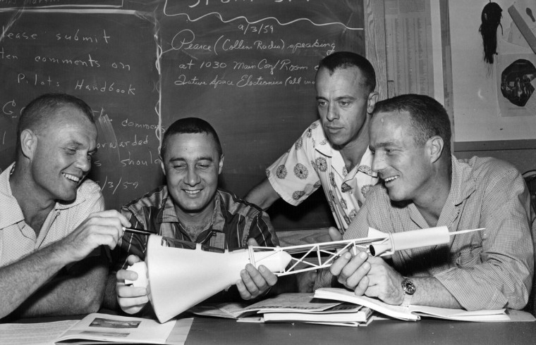 1959 - Left to right: John H. Glenn, Jr., Virgil J. Grissom, Alan B. Shepard, Jr., and Malcolm S. Carpenter. They are looking at model of capsule. (A. Aubrey Bodine/Baltimore Sun)