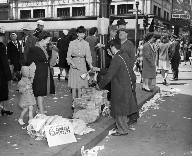 "1945 - VE DAY - Newspapers sold for 5 cents at Park Avenue and Lexington Street. Headline: ""All Germany Surrenders."" (A. Aubrey Bodine/Baltimore Sun)"