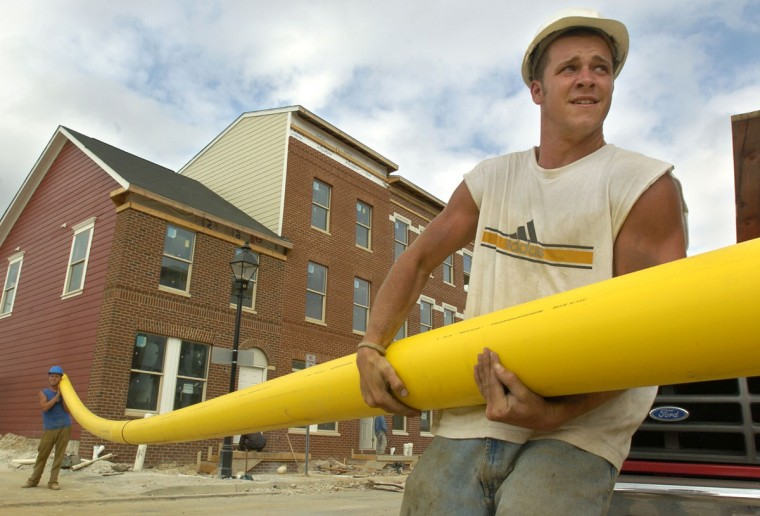 As part of the Flag House Courts revitalization project, a new community of townhomes is rising north of Little Italy. John O'Dea, in front, and Mike DiPietro, in back , utility technicians who work for a subcontractor, R. Norton Co., struggle with a long, heavy gas pipe they are installing in the 900 block of Granby St. (Baltimore Sun photo by Amy Davis, Sept. 7, 2004)