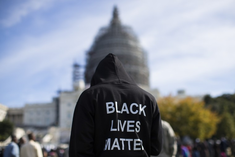 Neal Blair, of Augusta, Ga., stands on the lawn of the Capitol building during a rally to mark the 20th anniversary of the Million Man March, on Capitol Hill, on Saturday, Oct. 10, 2015, in Washington. Thousands of African-Americans crowded on the National Mall Saturday for the 20th anniversary of the Million Man March. (AP Photo/Evan Vucci)