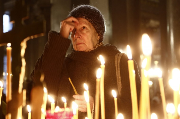 A woman prays as she lights a candle in a church in St. Petersburg during a day of national mourning for the plane crash victims in St. Petersburg, Russia, on Sunday, Nov. 1, 2015. A Russian passenger plane has crashed in the Sinai peninsula Saturday with 217 passengers, mostly Russians, and seven Russian crew members killed. (AP Photo/Dmitry Lovetsky)
