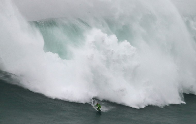US surfer Garrett McNamara rides a big wave during a tow-in surfing session at the Praia do Norte, or North beach, in Nazare, Portugal, Sunday, Nov. 1, 2015. McNamara set a world record for the largest wave surfed when he rode a 23.7 metre wave (78-foot) in Nazare in 2011. (AP Photo/Armando Franca)