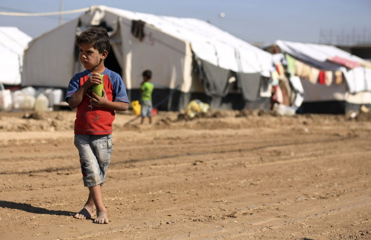 An internally displaced child eats a cucumber at a refugee camp that has partly become muddy due to recent heavy rains in Youssifiyah, 12 miles (20 kilometers) south of Baghdad, Iraq, Sunday, Nov. 1, 2015. Rain storms began late Wednesday and continued through the morning Thursday, dumping heavy rains on the Iraqi capital and across the country. (AP Photo/Hadi Mizban)