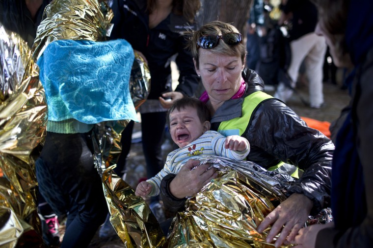 A volunteer wraps a baby in an emergency blanket for warmth as people disembark from a rubber boat from neighboring Turkey at a beach on the northern shore of Lesbos, Greece, Monday, Nov. 2, 2015. More than 300,000 people have traveled on dinghies and boats from nearby Turkey to Lesbos this year, with dozens dying along the way. (AP Photo/Marko Drobnjakovic)