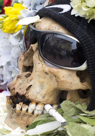 "A human skull or ""natitas"" with sun glasses and crowned with flowers is displayed outside the Cementerio General chapel, during the Natitas Festival, in La Paz, Bolivia, Sunday, Nov. 8, 2015. Although some natitas have been handed down through generations, many are from unnamed, abandoned graves that are cared for and decorated by faithful who use them as amulets believing they serve as protection. The tradition marks the end of the Catholic All Saints holiday, but is not recognized by the Catholic church. (AP Photo/Juan Karita)"
