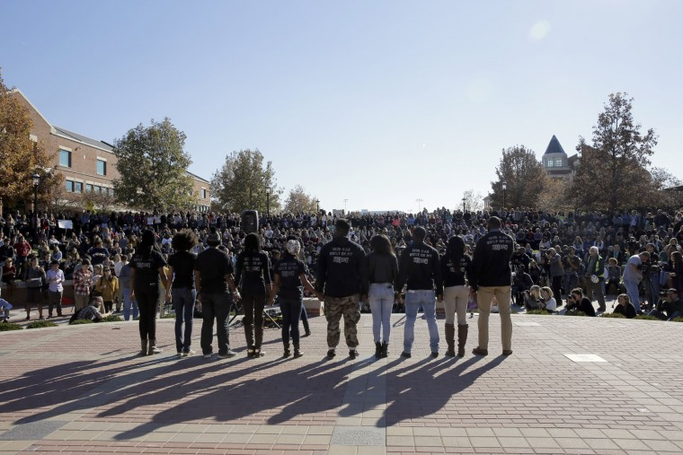 Members of black student protest group, Concerned Student 1950, hold hands following the announcement University of Missouri System President Tim Wolfe would resign Monday, Nov. 9, 2015, at the University of Missouri in Columbia, Mo. Wolfe resigned Monday with the football team and others on campus in open revolt over his handling of racial tensions at the school. (AP Photo/Jeff Roberson)