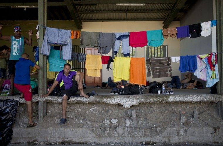 "Cuban migrants rest near the immigration office in PeÒas Blancas, Costa Rica, Tuesday, Nov. 17, 2015. More than 1,000 Cuban migrants heading north to the United States tried to cross the border from Costa Rica into Nicaragua, causing tensions to soar between the neighbors as security forces sought to turn them back. Nicaragua's government responded furiously on Sunday with a statement saying that Costa Rica ""had deliberately and irresponsibly thrown, and continues to throw"" the Cuban migrants into its territory, violating its national sovereignty. (AP Photo/Esteban Felix)"