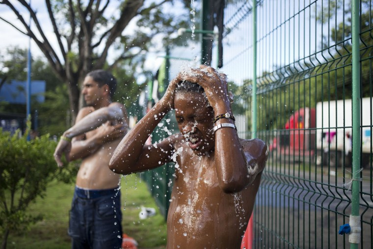 "A Cuban migrant Eliel Becker, bathes, using a provisional shower, set up outside the immigration office, in PeÒas Blancas, Costa Rica, Tuesday, Nov. 17, 2015. More than 1,000 Cuban migrants heading north to the United States tried to cross the border from Costa Rica into Nicaragua, causing tensions to soar between the neighbors as security forces sought to turn them back. Nicaragua's government responded furiously on Sunday with a statement saying that Costa Rica ""had deliberately and irresponsibly thrown, and continues to throw"" the Cuban migrants into its territory, violating its national sovereignty. (AP Photo/Esteban Felix)"