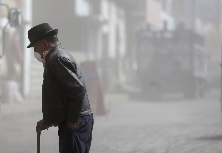 A man wears a mask as protection from the steady rain of volcanic ash spewed by the nearby Tungurahua volcano, as he crosses a street in Quero, Ecuador, Thursday, Nov. 19, 2015. Volcano monitors say about a dozen farming villages have been dusted with ash due to bursts from the Tungurahua. Thursday's report comes a day after authorities imposed new precautionary measures around the volcano, which has been increasingly restive. (AP Photo/Dolores Ochoa)