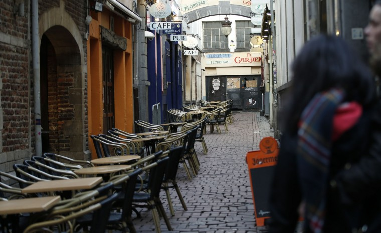 Tourists look down a side street off the normally bustling Rue des Bouchers in central Brussels, Monday, Nov. 23, 2015. Three days of the highest terror alert and unprecedented measures that have closed down the city's subways, schools and main stores, has created a very different atmosphere as the Belgian capital tries to avoid attacks similar to the ones that caused devastating carnage in Paris. (AP Photo/Alastair Grant)