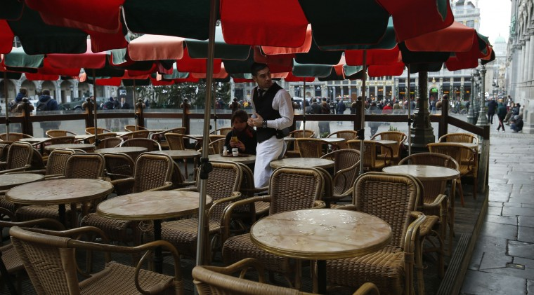 A waiter in a restaurant in the Grand Place serves a single customer on the outside terrace in central Brussels, Monday, Nov. 23, 2015. Three days of the highest terror alert and unprecedented measures that have closed down the city's subways, schools and main stores, has created a very different atmosphere as the Belgian capital tries to avoid attacks similar to the ones that caused devastating carnage in Paris. (AP Photo/Alastair Grant)