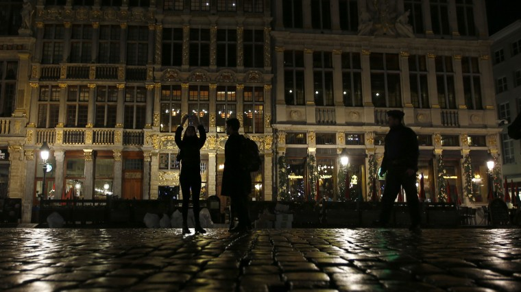 Tourists take a photo as a policeman, right, looks on in the Grand Place in Brussels, Monday, Nov. 23, 2015. The Belgian capital Brussels has entered its third day of lockdown, with schools and underground transport shut and more than 1,000 security personnel deployed across the country. (AP Photo/Alastair Grant)