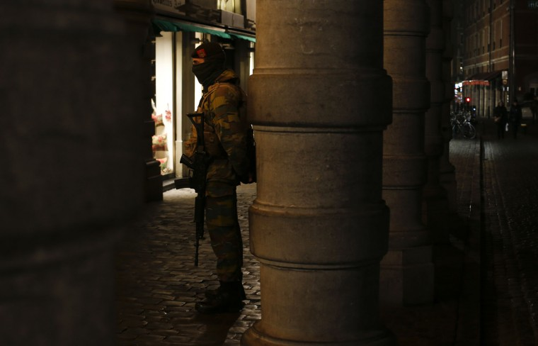A Belgian soldier waits for his colleague as he patrols near the Grand Place in Brussels, Monday, Nov. 23, 2015. The Belgian capital Brussels has entered its third day of lockdown, with schools and underground transport shut and more than 1,000 security personnel deployed across the country. (AP Photo/Alastair Grant)