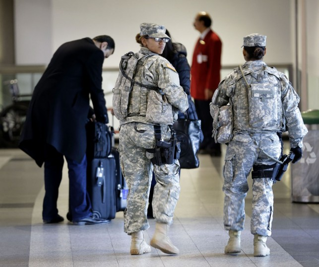 Military personnel walk through a terminal at LaGuardia Airport in New York, Tuesday, Nov. 24, 2015. (AP Photo/Seth Wenig)