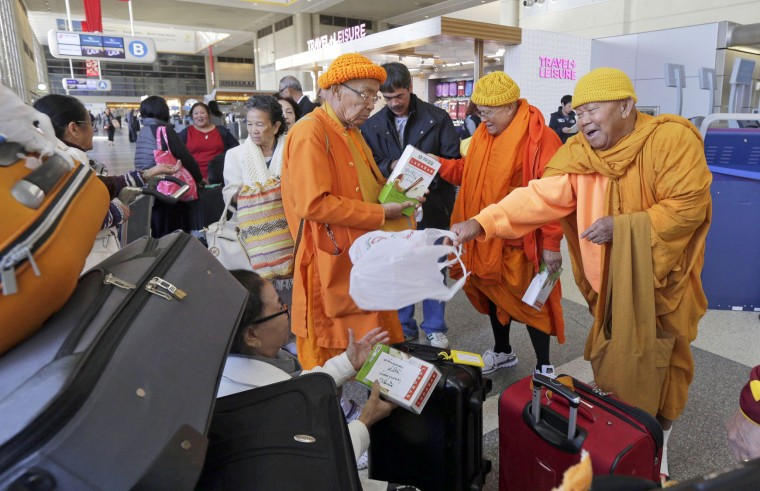 A group of Laotian monks prepare to leave Los Angeles International Airport for a flight to India, on Tuesday, Nov. 24, 2015. (AP Photo/Nick Ut)