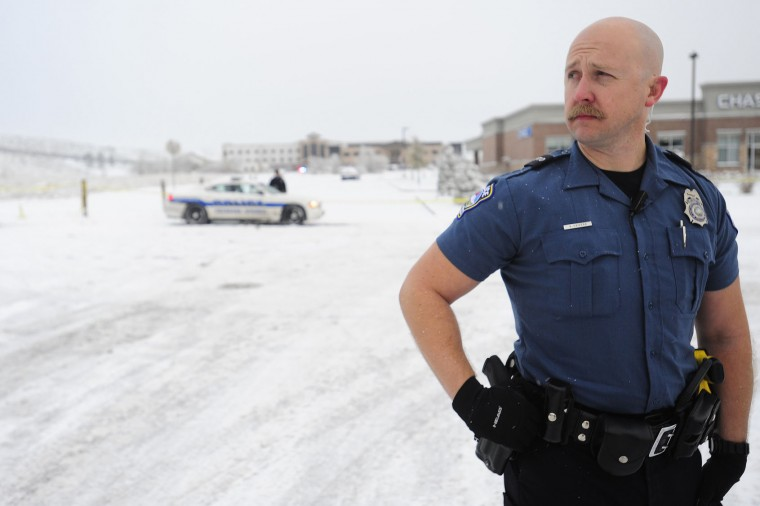 Officer Sandor Csikesz of the Colorado Springs Police Department guards the parameter as law enforcement officers continue the investigation on Saturday, Nov. 28, 2015, following Friday's shooting. The suspect, Robert Lewis Dear, surrendered to law enforcement and is now in police custody. (Daniel Owen/The Gazette via AP)