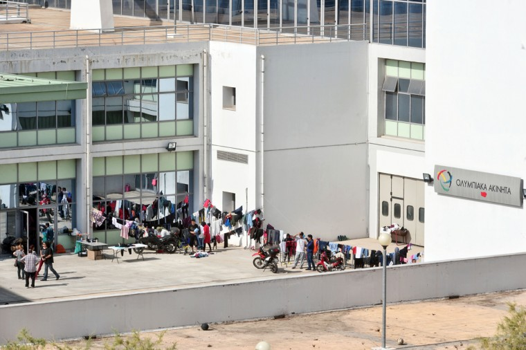 Immigrants and refugees at Galatsi Olympic Hall wait in line to be served lunch on October 7, 2015 in Athens, Greece. Greek authorities reopened the Galatsi Olympic Hall in a bid to accommodate some of the immigrants who have arrived in the country recently. About 800 people, mostly from Syria and Afghanistan, were bused to the stadium from Athen's central Victoria Square. (Photo by Milos Bicanski/Getty Images)