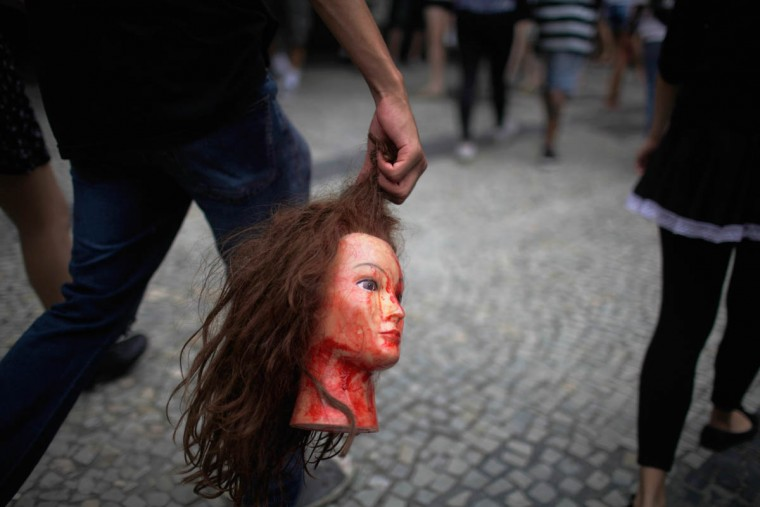 A reveler marches carrying a doll head during the annual 'Zombie Walk' as part of Day of the Dead festivities on November 2, 2015 in Rio de Janeiro, Brazil. Brazilians often mark the traditional Mexican holiday by visiting loved ones' graves and sometimes leaving offerings of food or drink. (Mario Tama/Getty Images)