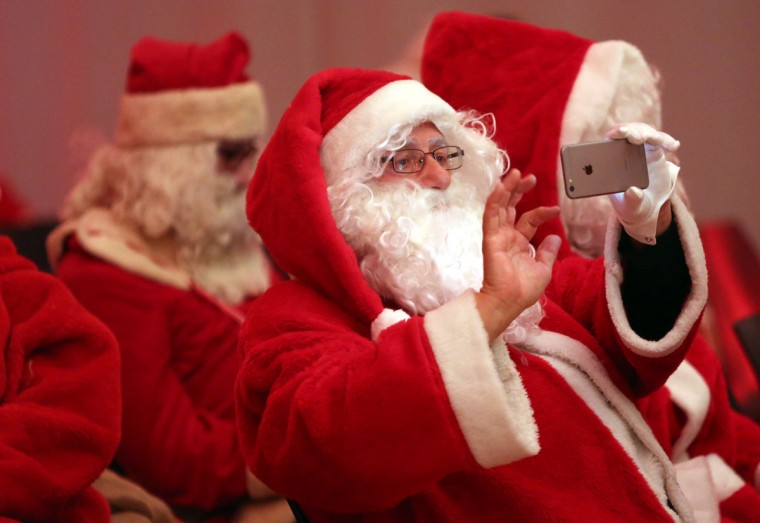 A participant takes a picture with his mobile phone during a gathering of volunteer student Santas and angels on November 28, 2015 in Berlin, Germany. (Photo by Adam Berry/Getty Images)