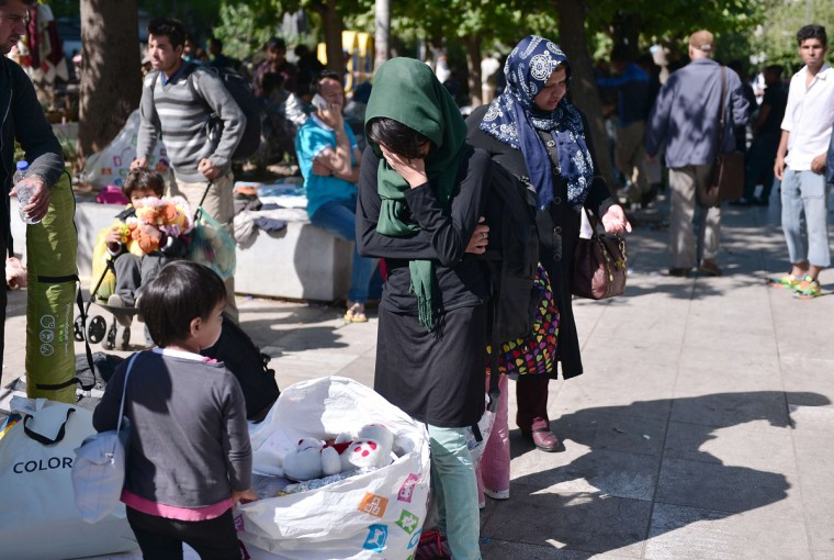 A migrant, stands next to her belongings , weeps as hundreds of migrants are forced to leave the Victoria Square to be transferred to a former Olympic hall, on October 1, 2015. Hundreds of mainly Afghan migrants had set up tents on Victoria Square in recent days, prompting protests from the city of Athens and local residents. Greek authorities hastily reopened a derelict sports hall from the Athens 2004 Olympics to house hundreds of migrants who were sleeping on the streets of the capital. (Louisa Gouliamaki/AFP/Getty Images)