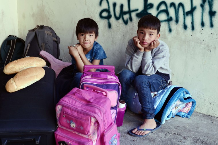 Afghani boys wait with their belongings at the Victoria Square in central Athens to be transferred to a former Olympic hall, on October 1, 2015. Hundreds of mainly Afghan migrants had set up tents on Victoria Square in recent days, prompting protests from the city of Athens and local residents. Greek authorities hastily reopened a derelict sports hall from the Athens 2004 Olympics to house hundreds of migrants who were sleeping on the streets of the capital. (Louisa Gouliamaki/AFP/Getty Images)