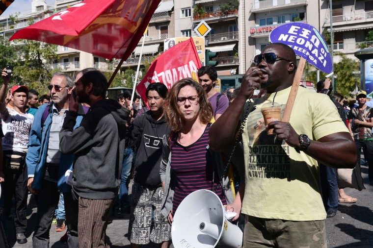 Pro-migrant groups chant slogans in the Victoria square in central Athens, where hundreds of migrants are forced to be transferred to a former Olympic hall, on October 1, 2015. Hundreds of mainly Afghan migrants had set up tents on Victoria Square in recent days, prompting protests from the city of Athens and local residents. Greek authorities hastily reopened a derelict sports hall from the Athens 2004 Olympics to house hundreds of migrants who were sleeping on the streets of the capital. (Louisa Gouliamaki/AFP/Getty Images)
