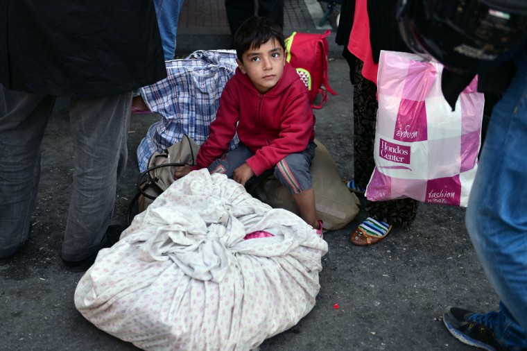 A child sits next to his family's belongings at the Victoria square in central Athens, as hundreds of migrants wait to be transferred to a former Olympic hall, on October 1, 2015. Hundreds of mainly Afghan migrants had set up tents on Victoria Square in recent days, prompting protests from the city of Athens and local residents. Greek authorities on October 1, 2015 hastily reopened a derelict sports hall from the Athens 2004 Olympics to house hundreds of migrants who were sleeping on the streets of the capital. (Louisa Gouliamaki/AFP/Getty Images)