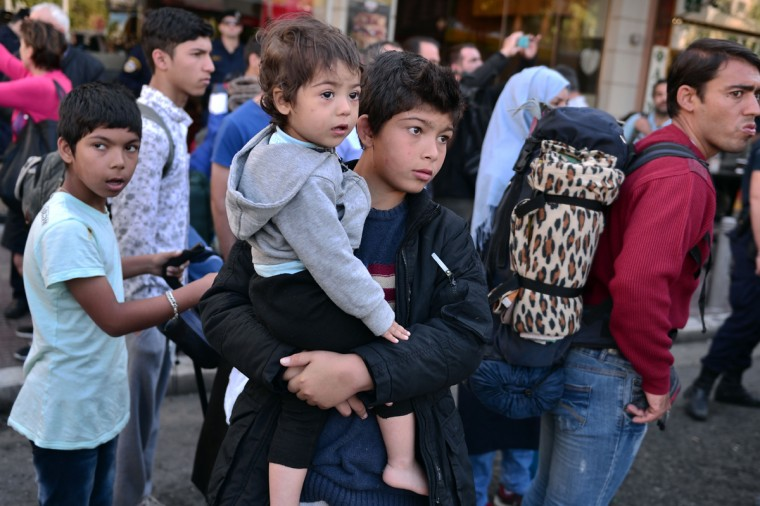 Hundreds of migrants wait to board buses before being transferred to a former Olympic hall from central Athens Victoria square, on October 1, 2015. Hundreds of mainly Afghan migrants had set up tents on Victoria Square in recent days, prompting protests from the city of Athens and local residents. Greek authorities on October 1, 2015 hastily reopened a derelict sports hall from the Athens 2004 Olympics to house hundreds of migrants who were sleeping on the streets of the capital. (Louisa Gouliamaki/AFP/Getty Images)