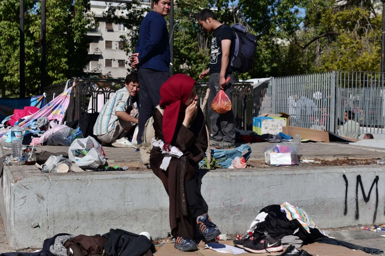 A migrant woman sits, as hundreds of migrants evacuate their camp at Victoria square in central Athens, before being transferred to a former Olympic hall, on October 1, 2015. Hundreds of mainly Afghan migrants had set up tents on Victoria Square in recent days, prompting protests from the city of Athens and local residents. Greek authorities on October 1, 2015 hastily reopened a derelict sports hall from the Athens 2004 Olympics to house hundreds of migrants who were sleeping on the streets of the capital. (Louisa Gouliamaki/AFP/Getty Images)